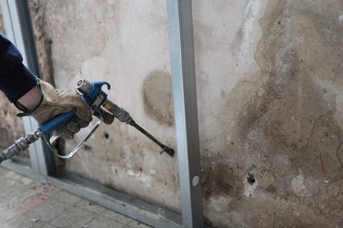 Man spraying inslation into walls