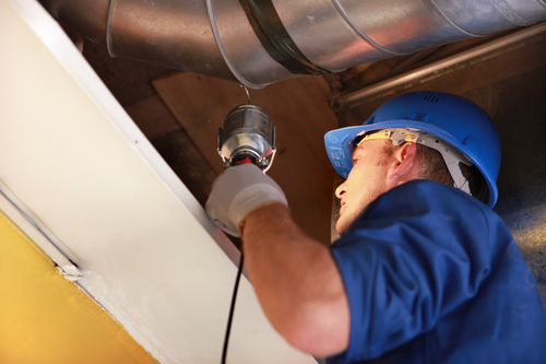 worker examining and estimating attic insulation. towson maryland insulation company